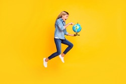 Full length body size photo of amazed jumping high schoolgirl keeping globe pointing on continent shouting amazed isolated on bright yellow color background