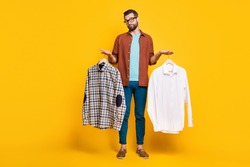 Full length body size photo of bearded consumer keeping two shirts comparing deciding isolated on bright yellow color background
