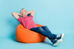 Full length body size photo of bearded man getting rest at work in beanbag isolated pastel blue color background