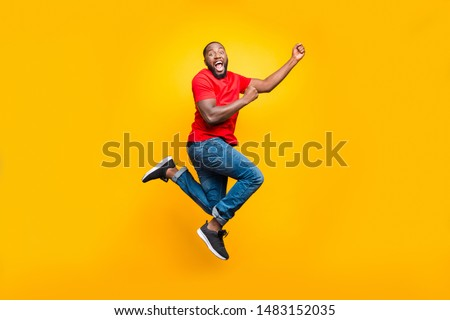 Full length body size photo of black man wearing red t-shirt having caught something invisible and now dragging it while isolated with yellow vivid background