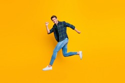 Full length body size photo of cheerful attractive handsome guy going jumping somewhere trendy wearing jeans denim isolated over vivid color background