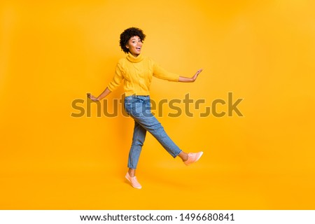 Full length body size photo of cheerful black afro american woman dancing or moving forward wearing jeans denim yellow pullover sneakers isolated with vivid color yellow background