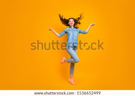 Full length body size photo of cheerful charming fascinating girl throwing her hair standing on one foot with positive facial expression isolated over yellow vivid color background