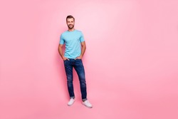 Full length body size photo of cheerful confident guy holding hands in jeans pockets wearing white footwear isolated pastel color background