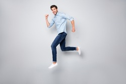 Full length body size photo of cheerful ecstatic crazy overjoyed man aspiring running jumping up in footwear isolated over grey color background
