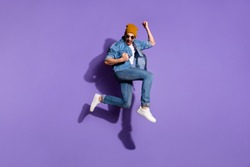 Full length body size photo of cheerful ecstatic screaming guy wearing jeans denim jacket overjoyed with victorious glory jumping up brown cap isolated over purple vivid color background