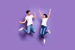 Full length body size photo of cheerful excited ecstatic positive crazy people in white footwear t-shirt jeans denim brown hair jumping screaming yeah isolated pastel color violet background