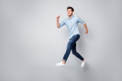 Full length body size photo of cheerful handsome attractive guy wearing white sneakers isolated over grey color background running towards his dream
