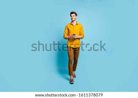 Full length body size photo of cheerful handsome guy addicted to his phone held in hands smiling toothily moving towards you wearing pants trousers isolated over pastel color background