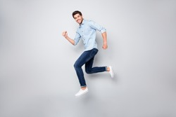 Full length body size photo of cheerful nice excited ecstatic man overjoyed with being able to jump and run in footwear high isolated over grey color background