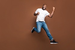 Full length body size photo of cheerful positive excited crazy ecstatic overjoyed man rejoicing about having bought new discounted jeans denim footwear white t-shirt jumping running color background