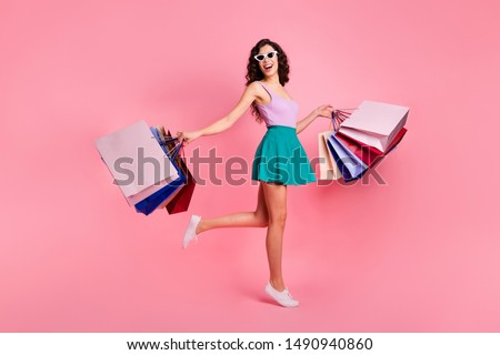 Full length body size photo of cheerful trendy stylish carefree cute attractive gorgeous woman rejoicing with sales wearing teal skirt while isolated with pastel background