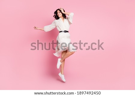 Full length body size photo of cheerful woman in long dress jumping looking empty space isolated pastel pink color background Сток-фото ©