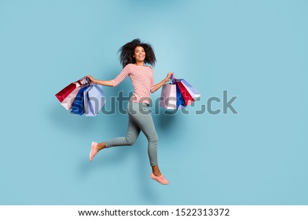 Full length body size photo of crazy cheerful nice cute fascinating nice youngster having returned from black friday mall in striped t-shirt pants trousers footwear isolated pastel color background