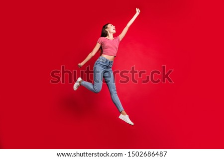 Full length body size photo of ecstatic stylish trendy beautiful charming cute lady trying to catch something while stretching isolated with red background