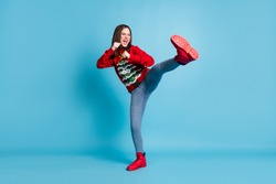 Full length body size photo of funny female student pretending to fight karate keeping one leg up shouting loudly wearing xmas outlook isolated on blue color background
