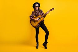 Full length body size photo of happy brunette playing acoustic guitar overjoyed isolated vibrant yellow color background