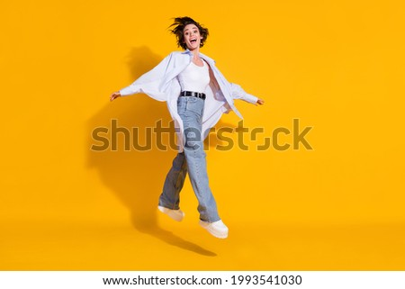 Full length body size photo of happy female student jumping stepping forward white shirt isolated on vivid yellow color background