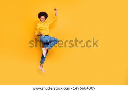 Full length body size photo of jumping curly wavy strong and powerful black woman rejoicing with her victorious glory fame wearing jeans denim pullover isolated bright color background