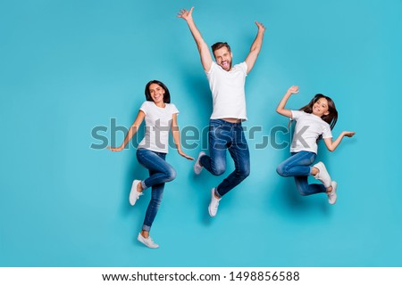 Full length body size photo of jumping enjoying nice glad family cute wearing white t-shirts jeans denim while isolated with blue background
