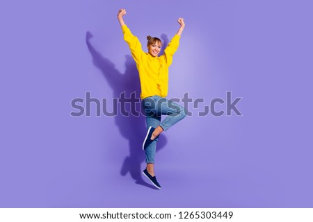 Full length body size photo of jumping high crazy cheer she her lady with pretty buns hairdo hands raised great big win wearing casual jeans yellow pullover isolated on purple background