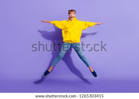 Full length body size photo of jumping high crazy cheer she her lady with pretty buns hairdo really need celebrating friday night wearing casual jeans yellow pullover isolated on purple background