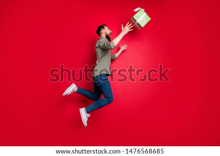 Full length body size photo of man trying to catch his prize gift while isolated with red background Сток-фото ©
