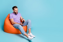 Full length body size photo of millennial playing console controller sitting in beanbag isolated on vivid blue color background empty space