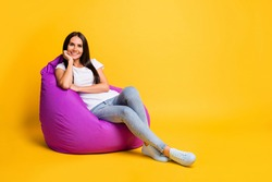 Full length body size photo of pretty brunette chilling in violet beanbag on pause isolated on bright yellow color background