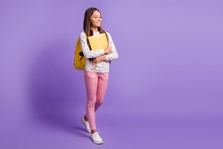 Full length body size photo of schoolgirl hugging book wearing backpack smiling isolated on bright violet background