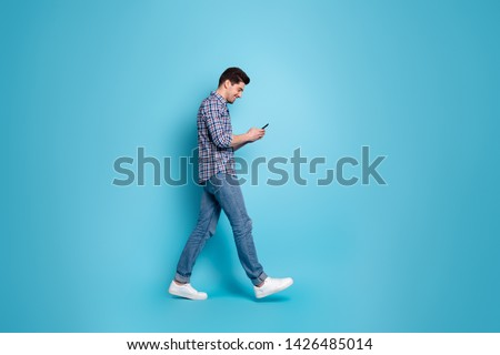 Full length body size photo of slender positive handsome carefree glad optimistic guy holding using telephone in hands going somewhere isolated pastel background