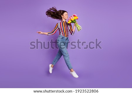 Full length body size photo of woman jumping high smelling tulip flowers scent isolated bright violet color background