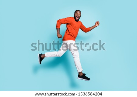 Full length body size photo side profile of man mixed-race expressing positive emotions wearing sneakers white trousers pants running jumping to discounts isolated vivid blue color background