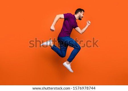 Full length body size photo side profile of urgent man running towards shopping center in blue pants foot wear jumping isolated vivid color background