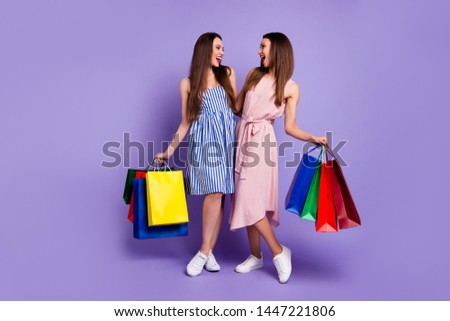 Full length body size photo two people beautiful she her models chic ladies carry many packs friendly mood laugh laughter wear casual summer colorful dresses isolated purple violet bright background