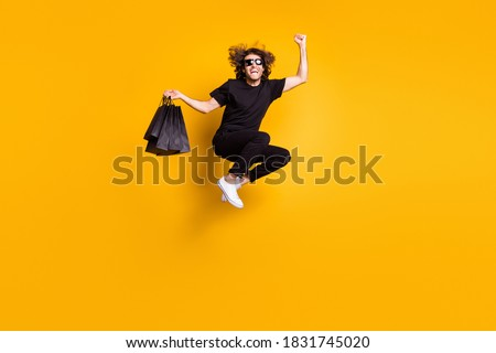 Full length body size portrait of man jumping shouting loudly celebrating great discount on black friday sale isolated on bright yellow color background