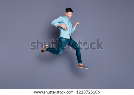 Full length body size portrait of nice attractive handsome cheerful positive man wearing blue formal shirt flying in air pretending playing instrument isolated over pastel grey violet background
