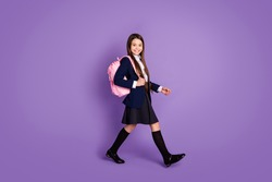 Full length body size profile side view of her she attractive cheerful small little schoolchild going back to school new season semester isolated violet lilac purple pastel color background