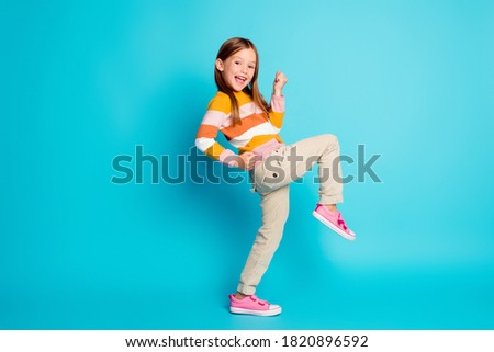 Full length body size profile side view of her she nice attractive pretty lucky glad cheerful cheery girl celebrating great success isolated over bright vivid shine vibrant blue color background