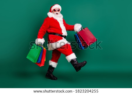 Full length body size profile side view of his he nice fat overweight cheerful glad Santa carrying bags Eve Noel gifts presents surprise festive newyear tradition isolated over green color background