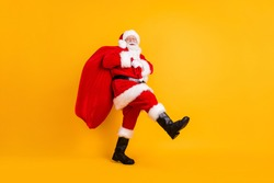 Full length body size profile side view of his he nice funny cheerful white-haired Santa St Nicholas going carrying big large sack sale shop isolated bright vivid shine vibrant yellow color background