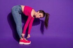 Full length body size profile side view of lovely girl bending sending air kiss fixing shoe cord isolated over bright violet color background