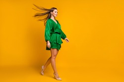 Full length body size profile side view of nice attractive pretty elegant cheerful straight-haired girl going wind blowing hair isolated over bright vivid shine vibrant yellow color background