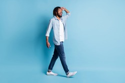 Full length body size profile side view of nice cheerful guy walking looking far isolated over bright blue color background