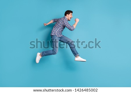Full length body size profile side view photo handsome cute guy shout feel content candid rejoice free time holidays weekend spring wear checked modern shirt denim sneakers isolated blue background
