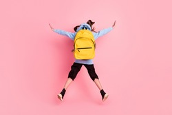 Full length body size rear back behind view of nice girl jumping new academic school year isolated over pink pastel color background