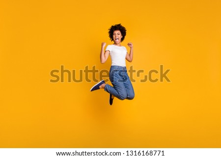 Full length body size side profile photo jumping high beautiful she her lady yelling loud voice hands arms up win wearing casual jeans denim white t-shirt clothes isolated yellow bright background #1316168771