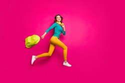 Full length body size side profile photo of cheerful positive nice pretty cute youngster wearing yellow pants trousers smiling toothily isolated pink vibrant color background