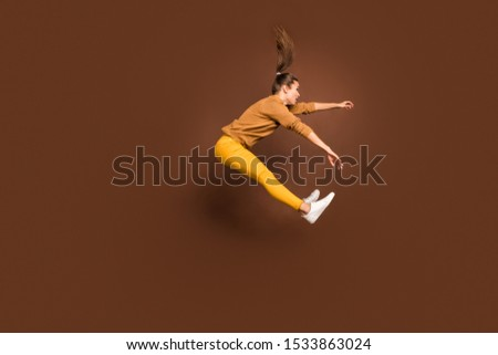 Full length body size side profile photo of frightened girl being pushed by strong gust of wind blown away isolated over brown pastel color background #1533863024