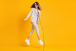 Full length body size side profile photo of girl jumping with mic singing on concert isolated on vibrant color background